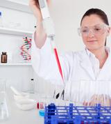 Cute female biologist holding a manual pipette with sample from test tubes - stock photo