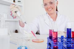 Gorgeous red-haired scientist using a pipette - stock photo