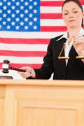 Portrait of a cute judge knocking a gavel and holding scales of justice - stock photo