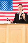 Young judge knocking a gavel and holding scales of justice - stock photo