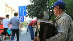Blind man playing accordion on European street (HD)c Stock Footage