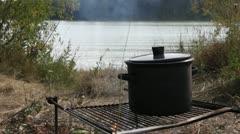 Pot on fire near Siberian river Stock Footage