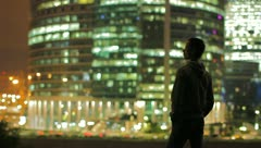 The young man and sky-scrapers background at night, time lapse Stock Footage
