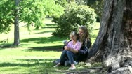 Mother and his daughter holding a pinwheel in a park Stock Footage