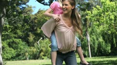 Mother holding her daughter on her back Stock Footage
