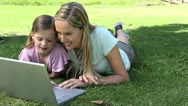 Mother and his daughter using a laptop in a park Stock Footage