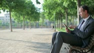 Young businessman working on tablet computer in the park, tracking shot  HD Stock Footage