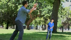 Father and his son playing football in a park - stock footage