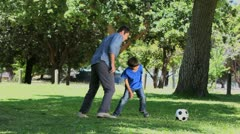 Son and his father playing football - stock footage