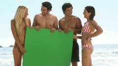 Friends holding a green board on the beach Stock Footage