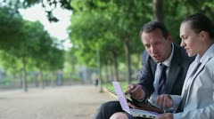 Business couple arguing in the park, tracking shot HD Stock Footage