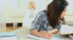 Woman studying while lying on the flloor Stock Footage