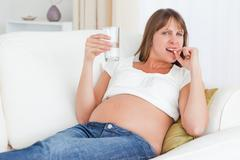 Charming pregnant woman taking a pill while lying on a sofa Stock Photos