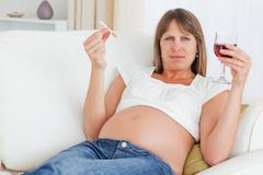 Charming pregnant woman holding a cigarette and a glass of red wine while lying Stock Photos