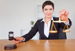 Serious woman with a gavel and the justice scale - stock photo