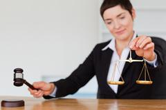 Serious judge with a gavel and the justice scale - stock photo