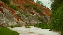 Asian woman walking  in river canyon with red, orange, white rocks. Vietnam Stock Footage