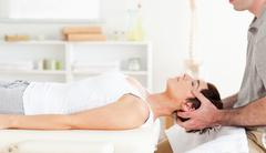 Chiropractor stretching a cute woman - stock photo