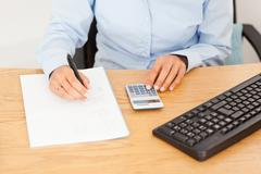 Female accountant writing results on a piece of paper Stock Photos
