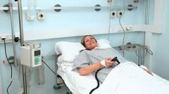 Female patient lying on a bed while looking at camera Stock Footage