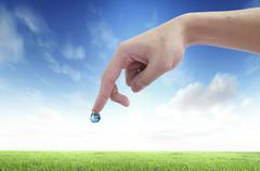 Stock Illustration of drop of water with earth inside and hand. the symbol of save planet