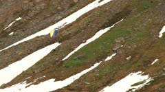 Paraglider Glides by Rocky Rugged Mountain Face 1a Stock Footage