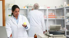 Female pharmacist holding a drug box while smiling Stock Footage