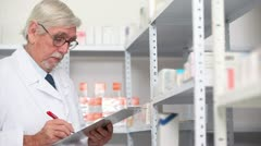 Pharmacist looking at pills in a shelf Stock Footage