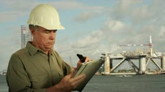 Oilfield worker on phone and using a tablet pc Stock Footage
