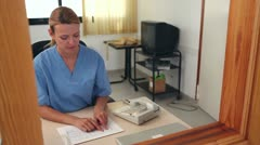 Nurse looking at files at a reception desk Stock Footage