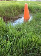 Orange cone in puddle Stock Photos