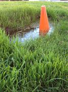 Orange cone in puddle - stock photo