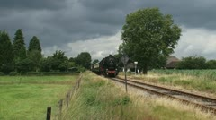 Steam train riding towards and from camera and whistling 03p Stock Footage