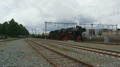 Steam train riding towards and from camera at railway station 04i Stock Footage