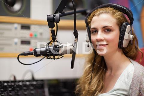 Stock photo of Young woman posing with a microphone