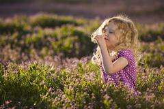 Caucasian girl smelling flowers - stock photo