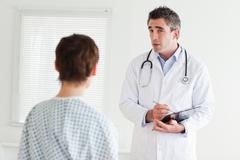 Serious Doctor talking to a woman in hospital gown - stock photo