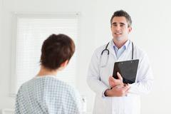 Doctor talking to a woman in hospital gown - stock photo