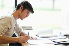 Serious male student writing Stock Photos