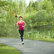 Caucasian athlete running with Olympic torch on park path Stock Photos