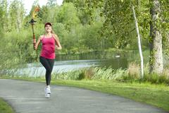 Caucasian athlete running with Olympic torch on park path - stock photo