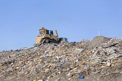Heavy industrial equipment ontop of mountain of household trash and garbage Stock Photos