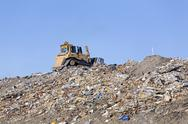 Stock Photo of Heavy industrial equipment ontop of mountain of household trash and garbage