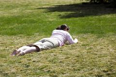 Girl laying on grass early spring bare foot 9060.jpg Stock Photos