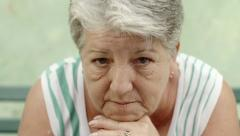 Portrait of sad old woman with white hair on bench - stock footage