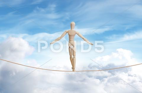 Stock Illustration of wooden model standing on a rope over the cloud sky