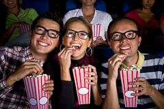 Hispanic friends enjoying popcorn at movie theater Stock Photos