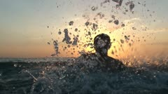 Man have water fun at sunset Stock Footage