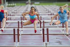 Runners jumping hurdles in race Stock Photos