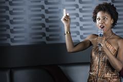 African American woman singing karaoke in nightclub Stock Photos